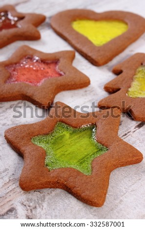 Fresh homemade decorated stained glass gingerbread, Christmas cookies on old white wooden background, christmas time - stock photo