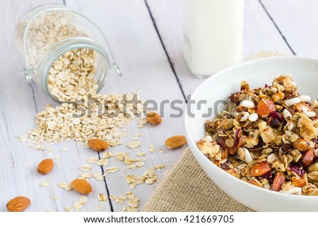 Fresh homemade granola with a glass of milk and a jar of oat in the background - stock photo