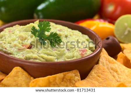 Fresh homemade guacamole, a Mexican sauce made of avocado, onion and tomato, garnished with fresh cilantro leaf, nachos around and ingredients in the back (Selective Focus, Focus on the cilantro leaf) - stock photo