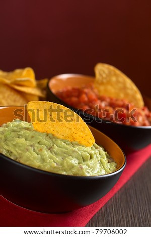Fresh homemade guacamole, a Mexican sauce made of mainly avocado cream with a nacho on top with a tomato sauce in the back (Selective Focus, Focus on the nacho in the guacamole) - stock photo