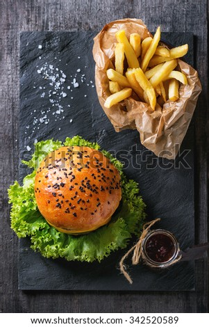 Fresh homemade hamburger with black sesame seeds and french fries potatoes in backing paper, served with ketchup sauce in glass jar and sea salt on black slate board over wooden surface. Top view - stock photo