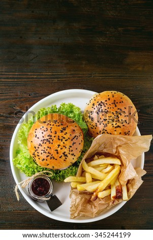 Fresh homemade hamburger with black sesame seeds in white plate with french fries potatoes, served with ketchup sauce in glass jar over dark wooden table. Top view - stock photo