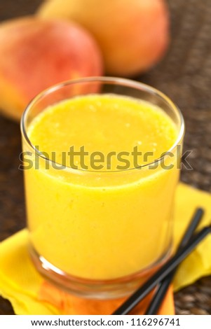 Fresh homemade mango juice in glass with straws on the side and mango fruits in the back (Selective Focus, Focus on the front rim of the glass)