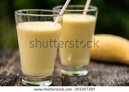 Fresh homemade mango  smoothie in a glass, served outside in a garden on a wood table