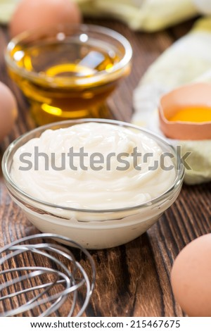 Fresh homemade Mayonnaise on an old wooden table (close-up shot) - stock photo