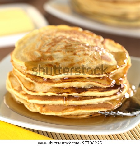 Fresh homemade pancakes with maple syrup (Selective Focus, Focus on the front of the upper three pancakes)