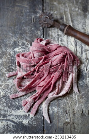 fresh homemade pasta tagliatelle with beetroot on rustic wooden table with flour - stock photo