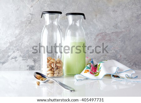 fresh homemade pistachio milk in a transparent bottle and pistachio nuts. vegetarian alternative to milk. - stock photo