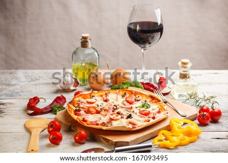 Fresh homemade pizza served with red wine - stock photo