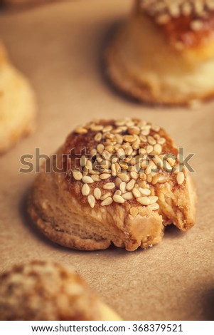 Fresh homemade salty scones with cheese and sesame, tasty baking food product on kraft paper, macro close up with selective focus