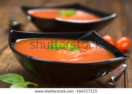 Fresh homemade tomato soup with basil leaf on top served in black bowl on dark wood (Selective Focus, Focus on the basil leaf on the tomato soup)  - stock photo