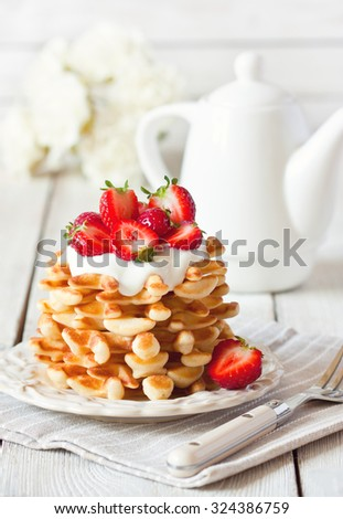 Fresh homemade waffles with whipped cream and strawberry. - stock photo