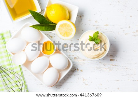 Fresh homemade white sauce Mayonnaise and ingredients eggs, lemon olive oil on white background. Top view - stock photo