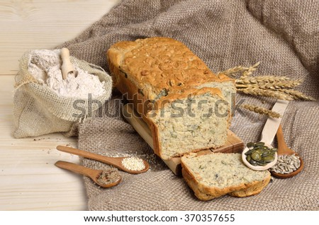 Fresh homemade whole grain bread with pumpkin, flax, sunflower and sesame seeds on jute cloth with sack of whole grain flour - stock photo