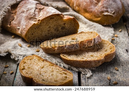 fresh homemade whole wheat bread on rustic background - stock photo