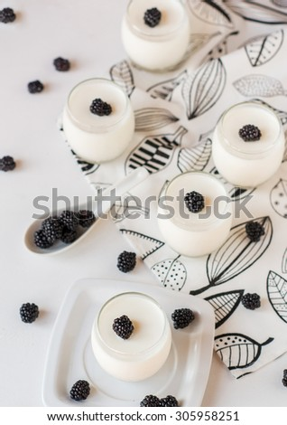 fresh homemade yoghurt with berries on white wooden background - stock photo