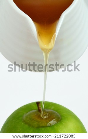 Fresh honey drop from honey pot on green apple during Rosh Hashanah Jewish holiday, on white background with copy space - stock photo