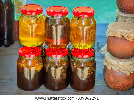Fresh honey of different varieties in glass jars with lids for sale at the fair.