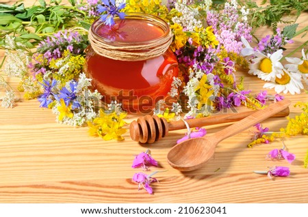 Fresh honey on wooden table with colorful flowers and spoons - stock photo