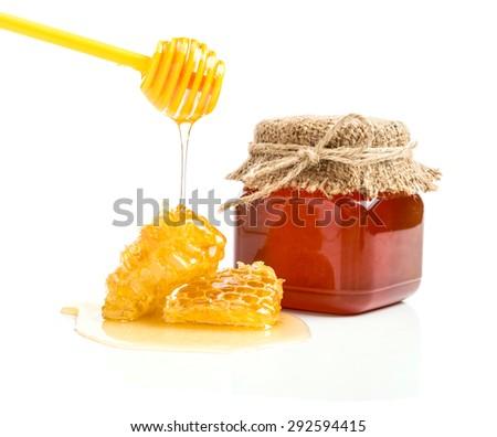 Fresh honey with honeycomb on white background. - stock photo