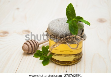 Fresh honey with mint on a wooden background - stock photo