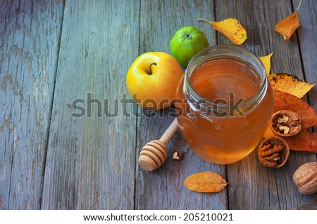 Fresh honey with pollen on an old wooden table. Autumn background with apples, nuts and honey. Rural motive with food and fallen leaves. - stock photo