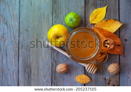 Fresh honey with pollen on an old wooden table. Autumn background with apples, walnuts and honey. Rural motive with food and fallen leaves. top view - stock photo
