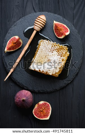 Fresh honey with ripe figs over black wooden surface, above view