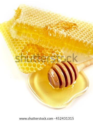Fresh honeycomb with a wooden dipper in a pool of healthy golden liquid honey on a white background in a close up high angle view - stock photo