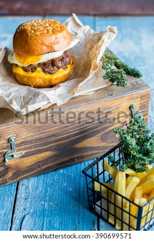 Fresh hot and tasty hamburger with fried eggs, cheese and meat on light blue rustic wooden background. Fried potatoes in front of it. Ideal lunch. - stock photo