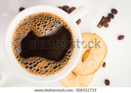 Fresh hot coffee with cookies and coffee beans around cup - top view - stock photo