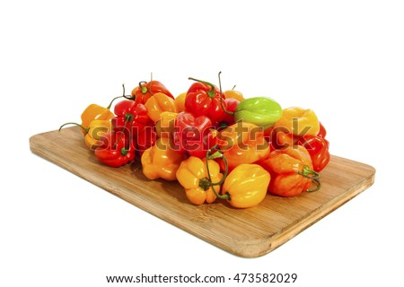 Fresh hot colorfull chili peppers on wooden board over white
