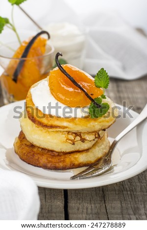 Fresh hot homemade pancakes slide in a white plate on a wooden background with white napkin