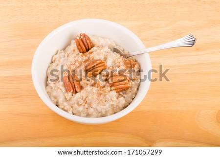 Fresh, hot oatmeal topped with pecan halves and cinnamon - stock photo