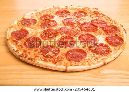Fresh, hot pepperoni pizza on a wood cutting board - stock photo