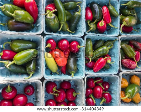 Fresh hot peppers in blue boxes at farm market. - stock photo