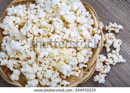 Fresh hot Popcorn in the basket on wood background - stock photo