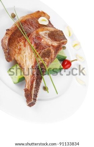 fresh hot roasted lamb meat fillet ready on china plate with tomatoes, green pepper , and garlic isolated  over white background