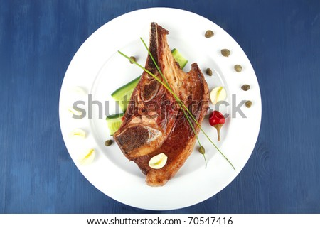 fresh hot roasted lamb meat fillet ready on china plate with tomatoes, green pepper , and garlic on blue wooden table - stock photo