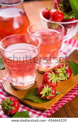 fresh hot strawberry compote with ripe red strawberry on wooden background