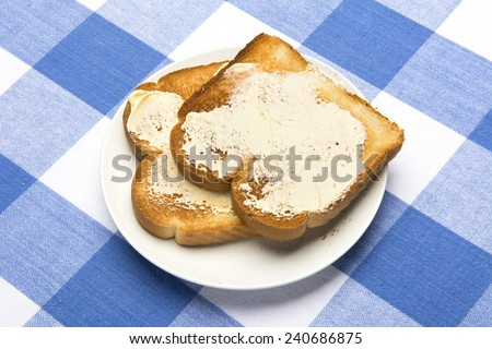 Fresh, hot toast spread with butter sits during mealtime to be consumed. - stock photo