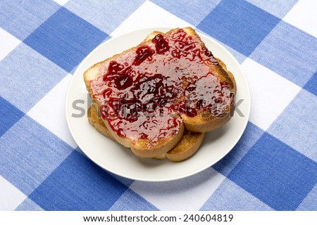 Fresh, hot toast spread with grape jelly sits during mealtime to be consumed.  - stock photo