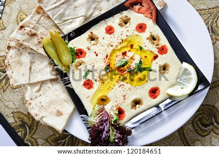 Fresh Hummus topped with olive oil and spices. - stock photo
