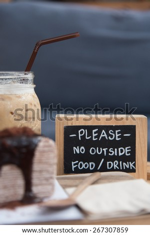 fresh iced coffee and delicious chocolate crape cake serve on wooden tray in coffee shop - stock photo