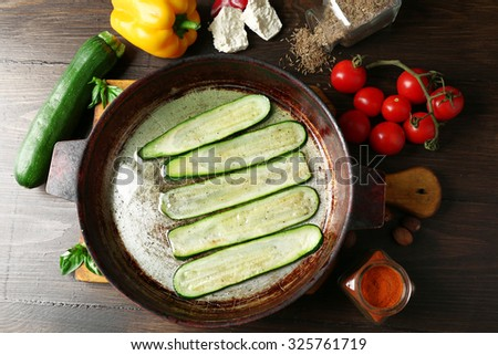 Fresh ingredients and fried zucchini slices for preparing zucchini rolls on wooden background  - stock photo
