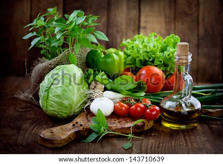 Fresh ingredients for cooking in rustic setting: tomatoes, basil, olive oil, garlic and onion,cabbage,letttuce - stock photo
