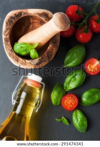 Fresh ingredients for cooking: tomato, salad and spices over stone background - stock photo