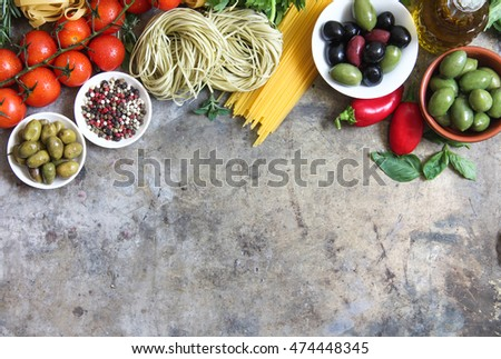 Fresh ingredients for italian cuisine: pasta, tomatoes, basil, olive oil, garlic and onion