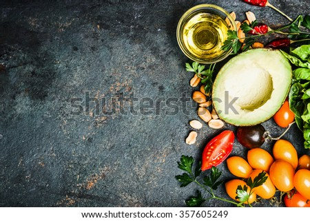 Fresh ingredients for salad or dip making: avocado, tomatoes,nuts,oil on rustic background, top view, place for text. Healthy food and cooking concept - stock photo