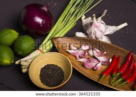 Fresh ingredients, lemon, onion, garlic, chili, lemon grass and tea for Thai cooking on wooden board. - stock photo